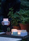 Selbstgemachte Windlichter aus Transparentpapier auf einem Tablett