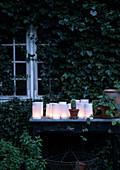 Laternen aus weißem Papier auf altem Tisch vorm Gartenhaus mit Efeu