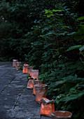 Windlichter in braunen Papiertüten am Weg im abendlichen Sommergarten