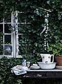 Rustic washing station on an old table at the garden shed with ivy