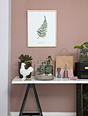 Terrarium mit Kakteen und Sukkulenten auf dem Schreibtisch vor Wand in Rosa