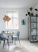 Blue spoke-back chairs at a dining table in front of a glass cabinet filled with crockery