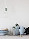 Light blue dishes, vases, and thistles on the kitchen shelf under the pendant light