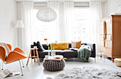 Bright living room with designer armchair, sofa and knitted pouf as a cooking table