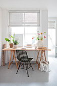Wooden table with chair in front of the window