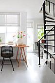 Wooden table with chair in front of the window, side spiral staircase