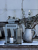 Lantern and jug made of sheet metal with eucalyptus branches