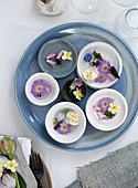 Various spring flowers in bowls on a blue plate