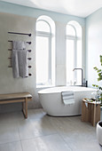 A free-standing bathtub in front of arched windows
