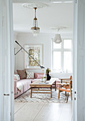 Pink upholstered sectional sofa, rustic coffee table, and leather chairs in the living room