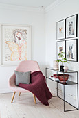 Pink upholstered chair with pillows and blanket, console table and pictures on the wall