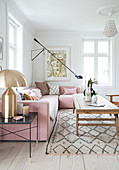 Pink upholstered suite, golden table lamp and rustic coffee table in the living room