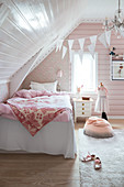 A bed in a girl's room decorated in pink and white