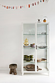 White display case with vintage crockery and rustic stool under a pennant chain
