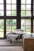 Wooden chest and day bed with blankets in the glass house
