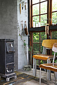 An old wood-burning stove and stacks of chairs in a glass house