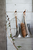 Garden tools and hand broom with shovel hanging on wooden wall