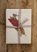 Geschenkverzierung mit gepressten Blättern und Blumen