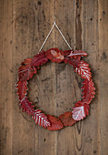 Wreath of red autumn leaves with white decoration