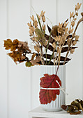 Dried flowers and twigs in a vase decorated with autumn leaves