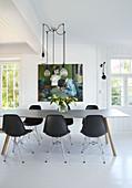 Esstisch mit schwarzen Stuhlklassikern, darüber Pendelleuchte in offenem Wohnraum
