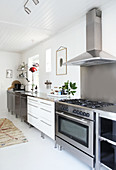 Küchenzeile mit Gasherd und Dunstabzughaube