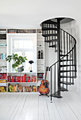 Black spiral staircase next to guitar and bookshelf