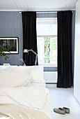 Double bed and black curtains in blue-grey bedroom