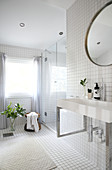 A washbasin and a round table in a white tiled bathroom