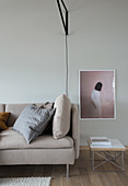 Light upholstered sofa, side table and photo art on the wall
