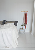 Double bed in minimalist bedroom with white floorboards