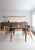 A black dining table with chairs in front of a brown sideboard