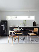 A round table with classic chairs in front of a dark kitchenette