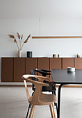 Black dining table with chairs in front of brown sideboard