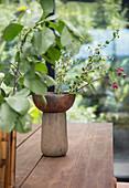 Vasen mit Blätterzweigen auf Holztisch