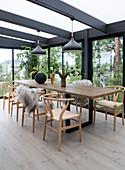 Selbstgebauter Esstisch aus Holz mit Klassikerstühlen im Wintergarten