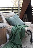 Cushions, animal fur and a plaid on a chair on a terrace