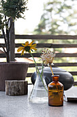 Flowers in glass jars and bottles on an outdoor table
