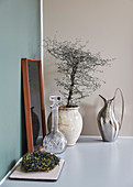 Crystal carafe and ceramic vessel with little tree and on a shelf