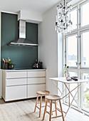 Filigraner Tisch mit Hockern vor Fenster und Küchenzeile mit Abzugshaube