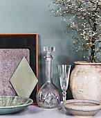 Kristallkaraffe und Glas, Keramikgefäß mit Bäumchen und Schalen auf Ablage