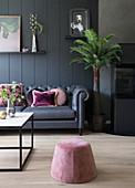 Dunkles Sofa mit Rosa Kissen vor dunkler Wand, Sitzpouf im Vordergrund