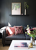 Dark sofa with pink cushions in front of dark wall