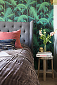 A bed with an upholstered headboard against jungle wallpaper