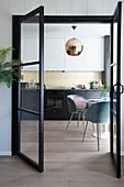 Blick durch offene Glastür in die Küche mit rundem Tisch und Schalenstühlen