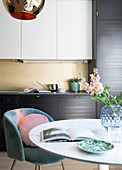 Round table with shell chair in front of the fitted kitchen