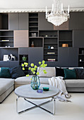 A dark living room wall with upholstered furniture a round coffee table and a chandelier