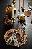 Gedeck und Kerzen auf herbstlich dekoriertem Tisch