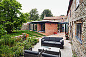 Garden view of extension and existing brick and flint farmhouse with patio furniture