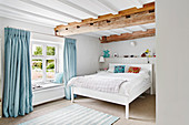 Bright and contemporary bedroom with painted beams and blue accents